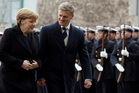 Angela Merkel dispenses her smiles sparingly, but the German Chancellor found herself beaming back at Bill English. Photo / AP