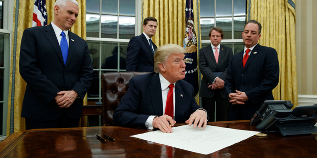 Vice President Mike Pence watches at left as President Donald Trump prepares to sign his first executive order. Photo / AP