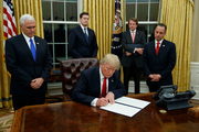 President Donald Trump, flanked by Vice President Mike Pence and Chief of Staff Reince Priebus, signs his first executive order on health care. Photo / AP