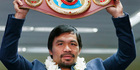 Filipino boxer Manny Pacquiao raises his WBO welterweight championship belt during a news conference. Photo/AP Photos