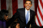 President Barack Obama walks up on stage with his wife Michelle and daughter Sasha. Photo / AP