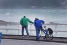 A pedestrian and cyclist struggle to make headway into the gale-force wind along Evan Bay Parade in Wellington. Photo/file
