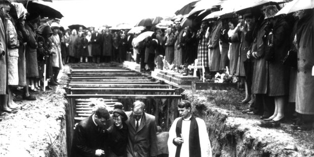 Accompanied by a clergyman, mourners leave the mass grave of the 19 miners killed in the Strongman Mine disaster on January 19, 1967. Photo / New Zealand Herald archive