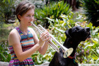 When Megan Burns plays the trumpet her biggest fan Ash, the Great Dane dog, likes to sing along. PHOTO/JOHN STONE
