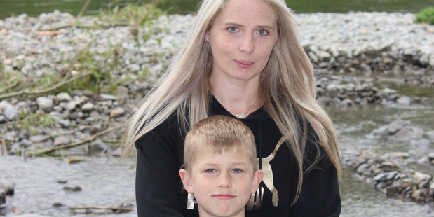 Jayden Shaw, 8, of Paraparaumu Beach School, with his mother Amanda Gibbons, at the Waikanae River where they were flipped from their rafts and into rapids. Photo / Cloe Willetts