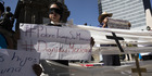 A demonstrator stands blindfolded with a sign that reads 'Poor Trump Without Mexico, Dignity Mexico' during a protest of President Donald Trump in Mexico City. Photo / Bloomberg