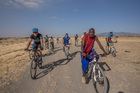 A Masai warrior leads Intrepid cyclists to his village. Photo / Lucy Piper