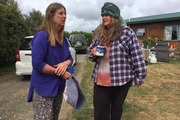 Comers Rd resident Helen Lee talks with neighbour Jani Dennis about the fire that claimed Lee's home and is now threatening Dennis' home.