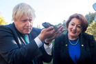 Boris Johnson gets up close and personal with a tuatara and Conservation Minister Maggie Barry. Photo / Pool