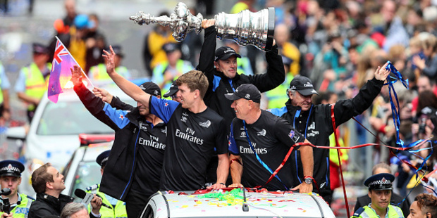 Loading Peter Burling (L) and Grant Dalton (R) celebrate as Glenn Ashby holds the Americas Cup during the Team New Zealand Americas Cup Welcome Home Parade. Photo / Getty Images