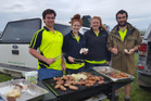 Handy Landys members Mac Thomson (left), Holly Smith, Jess Hill and Tim Craig cook a barbecue on the day of the tree planting in Kaikoura for all the volunteers. Photos / Handy Landys