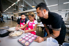 Michael Meredith of Eat My Lunch shares some of his cooking skills with Moeroa Tavai, 7, (left) and Betsy Fifita, 8, from Mangere Central School in Auckland. Photo / Dean Purcell