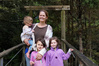 Jennifer Ives holding Lexi, with Gracie, left, and Milly on the swing bridge. Photo/Lindy Laird