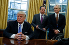 National Trade Council adviser Peter Navarro, right, and White House Chief of Staff Reince Priebus, centre, with US President Donald Trump. Photo / AP