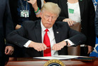 President Donald Trump takes the cap off a pen before signing executive order for immigration actions to build a border wall. Photo / AP