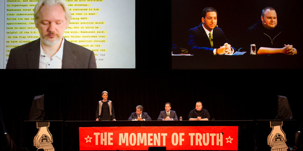 Wikileaks founder Julian Assange speaks via video link with Laila Harre (left at the table) during the 2014 Moment of Truth. Dotcom is at the far right.