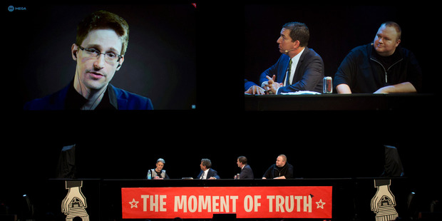 Former NSA contractor Edward Snowden via video link with Laila Harre (left at table) and Kim Dotcom (far right) during the Moment of Truth event in 2014.
