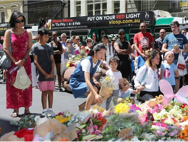 Visitors lay flowers at a shrine on Bourke St. Photo / News Corp Australia