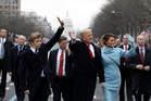 U.S. President Donald Trump waves to supporters as he walks the parade route with first lady Melania Trump and son Barron Trump. Photo / Getty