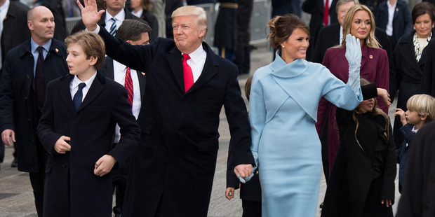 President Donald Trump and first lady Melania Trump, along with their son Barron, walk in their inaugural parade. Photo / Getty Images