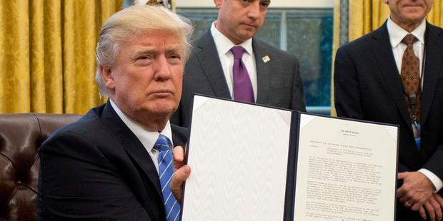 US President Donald Trump shows the Executive Order withdrawing the US from the Trans-Pacific Partnership (TPP). Photo / Getty