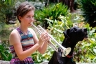 Megan Burns plays a few notes on her trumpet for family pet Ash.
