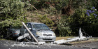 A car sits entangled in fallen powerlines in Marsden Ave, Mt Eden, after fierce wind and rain lashed Auckland on Saturday night. Photo / Michael Craig
