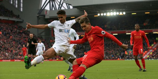 Swansea City's Kyle Naughton,left, and Liverpool's Roberto Firmino battle for the ball during the English Premier League soccer match between Liverpool and Swansea City. Photo / AP.