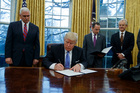 President Donald Trump signs an executive order to withdraw the US from the 12-nation Trans-Pacific Partnership trade pact. Photo / AP