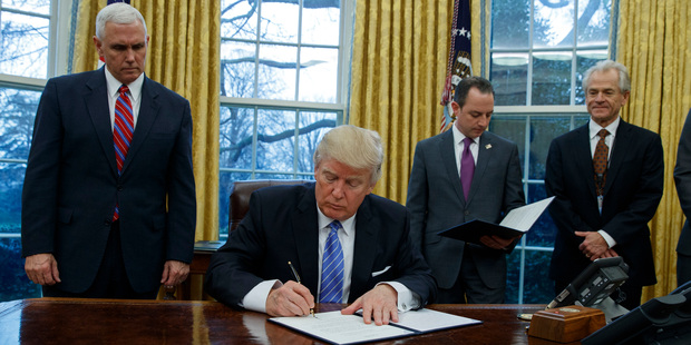 Loading President Donald Trump signs an executive order to withdraw the US from the 12-nation Trans-Pacific Partnership trade pact. Photo / AP