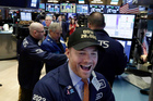 Specialist Frank Masiello wears a Dow 20,000 cap as he works on the floor of the New York Stock Exchange. Photo / AP