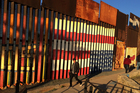 People pass graffiti along the border structure in Tijuana, Mexico. Photo / AP