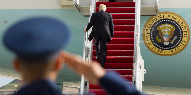 President Donald Trump is saluted as he walks up the stairs. Photo / AP