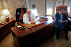 President Donald Trump, with his Chief of Staff Reince Priebus, sits at his desk on Air Force One upon their arrival at Andrews Air Force Base. Photo / AP