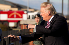 President Donald Trump shake hands with guests at the fence upon his arrival at Andrews Air Force Base. Photo / AP