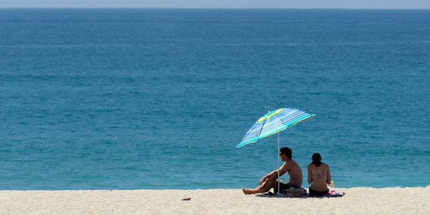 Loading Even the keenest of sunbathers were looking for shade on one of the hottest days of the year at Mt Maunganui beach, 13 January 2015 Photo / Alan Gibson