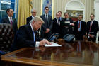 President Donald Trump signing executive orders in the Oval Office of the White House in Washington surrounded by his cabinet. Photo / AP