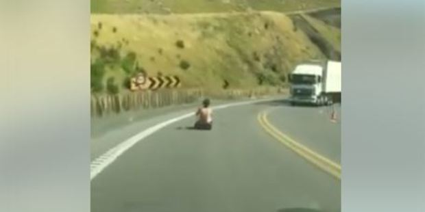 Loading Video footage of a shirtless man riding a luge down the Kaimai Range, as oncoming traffic approaches.