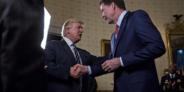 President Donald Trump shakes hands with James Comey, director of the FBI, during an inaugural reception in the Blue Room of the White House. Photo / Washington Post, Bloomberg