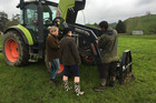 Nick Brown shows Tara Miller and Georgia Milne how to conduct a tractor pre-start check.