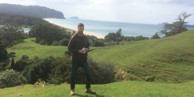 Catchment management officer Rob Corkill is based at the regional council's Whitianga office. He is standing in front of the entrance to Wharekawa Harbour, with Opoutere Beach behind him.