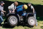 Three farmers grapple with a quad bike to right a rider. Research suggests quad bike riders need to be aware of, and plan for, human error.