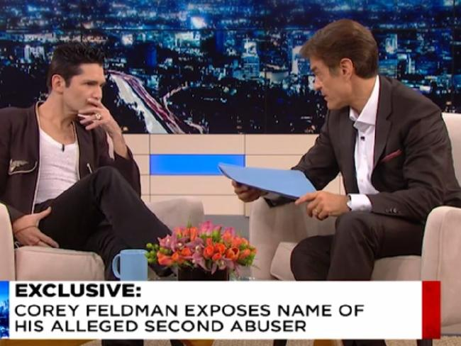 Corey Feldman appears on Dr Oz, who holds a blue envelope carrying the name of an alleged paedophile. Photo / Supplied via News.com.au