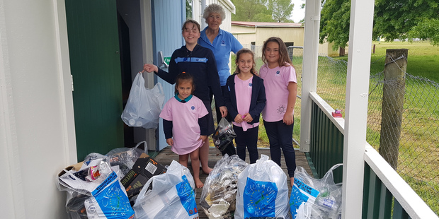 Kaitaia Girl Guides leader Dawn Pearce, back, with from left, Laurel Wilson, 13, Myah Thomas, 5, Stevie Thomas, 7 and Nova Tomars, 7, and some of the trash they picked up from the field behind their base in one day.  Photo / Mike Dinsdale