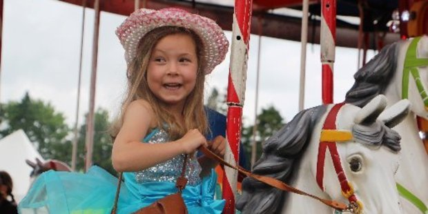 Isla Terrill is all smiles on the merry-go-round.