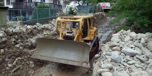 Bulldozers and excavators were being used by contractors in Reservoir Creek in the north end of Roxburgh yesterday afternoon to clear rocks from the area. Photo: Tom Kitchin
