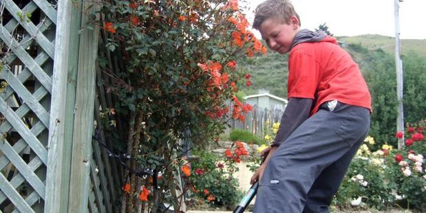 Loading Roxburgh Area School pupil Eli Halker (10) helps clean the garden of a Tweed St house yesterday. Photos: Tom Kitchin