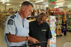 Constable Richard Avery helping Four Square owner Hitendra Patel with a shoplifting incident, one of his last tasks in Kaeo.