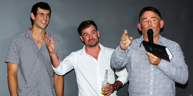 Auctioneer Andy Transom (right) takes bids for the services of Northern Districts' cricketers Zak Gibson (left) and Peter Bocock.