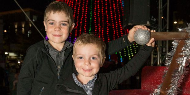 Hamish, 4, helped by big brother Elliott pulls the giant switch to light up Hamilton's 27m tall Christmas Tree in Garden Place on Saturday. Photo / Supplied